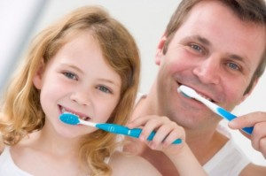 girl and man brushing teeth
